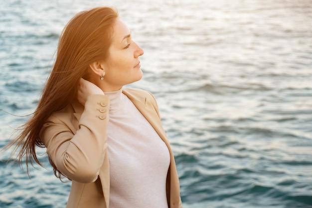 Wesoła kobieta dotyka długich włosów stojąc na nabrzeżu, ciesząc się piękną przyrodą na tle falującego morza, ekstremalnie bliski widok
