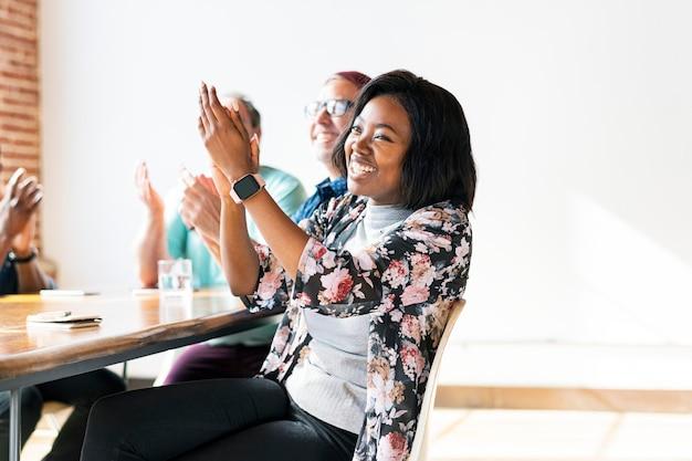 Wesoła kobieta klaszcze w dłonie na spotkaniu