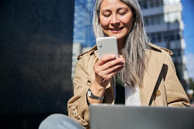 Wesoła kobieta korzystająca z telefonu komórkowego na ulicy