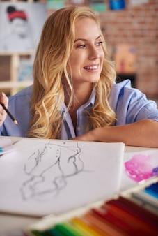 Wesoła kobieta nad swoimi rysunkami