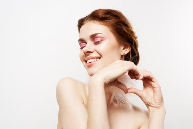 Wesoła kobieta nagie ramiona jasny makijaż puszyste kolczyki studio