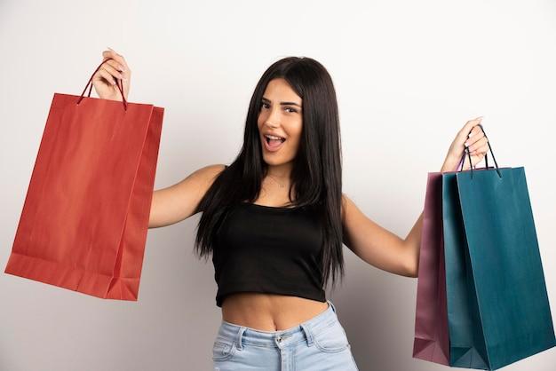Wesoła kobieta niosąca torby na zakupy na beżowym tle. wysokiej jakości zdjęcie