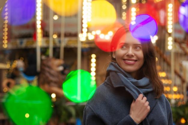 Wesoła kobieta nosi szary płaszcz spacerując na ulicy z bokeh światłem. pusta przestrzeń