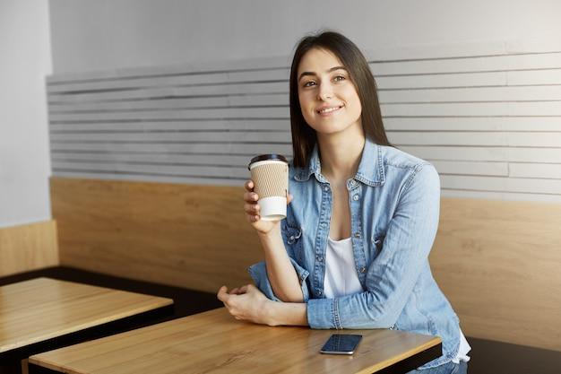 Wesoła kobieta o ciemnych włosach w modnych ubraniach siedząca w stołówce, pijąca kawę po długim dniu w pracy, marzycielsko wyglądająca na bok i myśląca o tym, co zrobiła dzisiaj. koncepcja stylu życia.