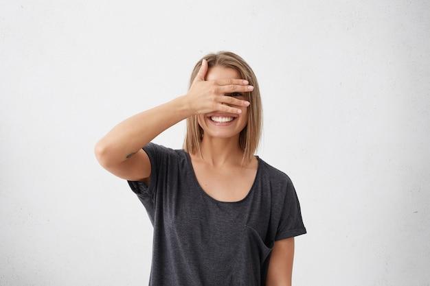 Wesoła kobieta o nieśmiałym spojrzeniu zaglądającym przez palce. zawstydzona młoda śliczna kobieta z fryzurą bob zakrywającą twarz ręką wyglądającą na zagubionego uśmiechniętego szeroko