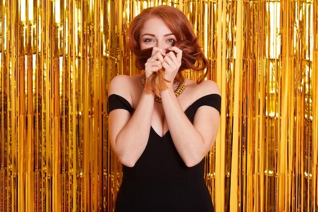 Wesoła kobieta o rudych włosach jest ubrana w czarną sukienkę, pozuje nad lśniącą zasłoną, bawi się w nocnym klubie, zakrywając twarz włosami, wyrażając pozytywne emocje i flirtując.