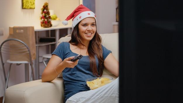 Wesoła kobieta ogląda telewizję i je frytki