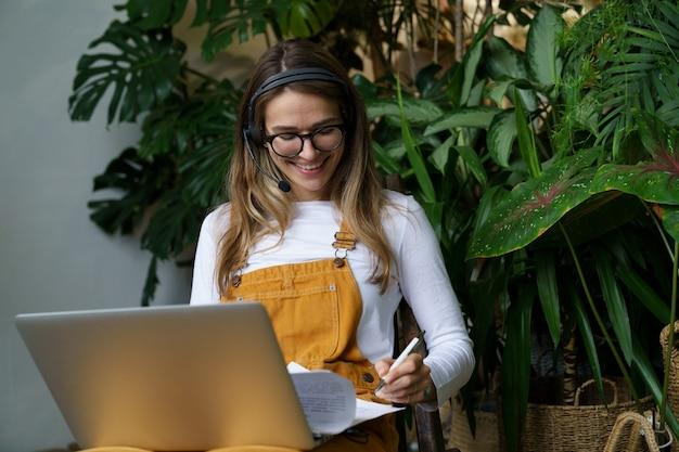 Wesoła kobieta, ogrodnik domowy lub dekorator kwiaciarni, omawia zdalnie budżet zamówienia z klientem online