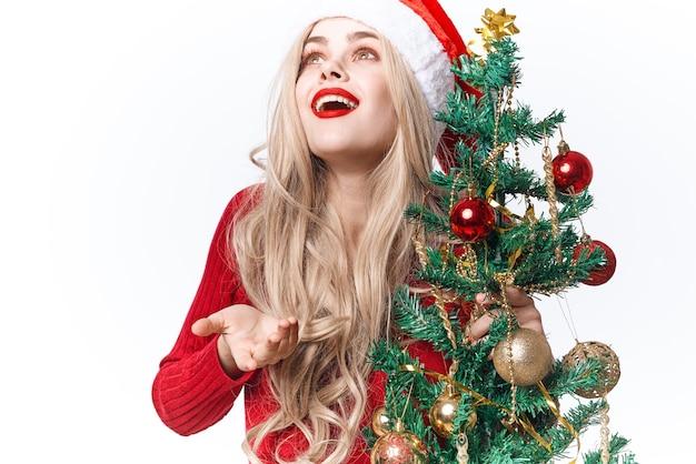 Wesoła kobieta ozdabia drzewo jasnym tłem zabawek