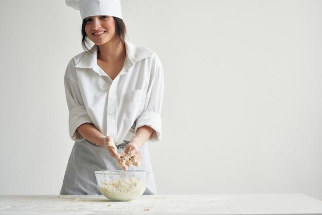 Wesoła kobieta piekarz w mundurze szefa kuchni toczy ciasto na stole pracy