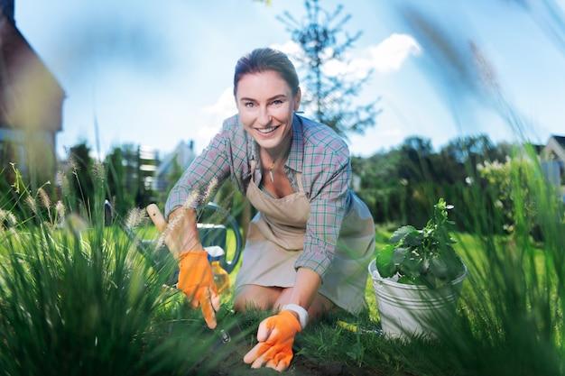 Wesoła kobieta. piękna wesoła zielonooka kobieta czuje się niesamowicie podczas pracy w ogrodzie i wyrywania chwastów