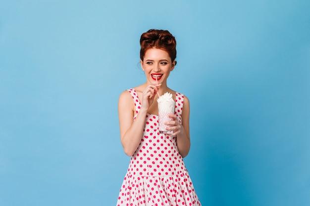 Wesoła kobieta pinup pijąca koktajl mleczny. strzał studio imbir dziewczyna w sukience w kropki na białym tle na niebieskiej przestrzeni.