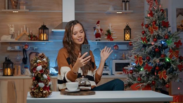 Wesoła kobieta podczas świątecznej rozmowy wideo z przyjaciółmi w domu