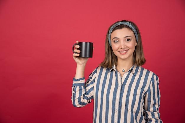 Wesoła kobieta pokazuje filiżankę kawy i pozuje do przodu