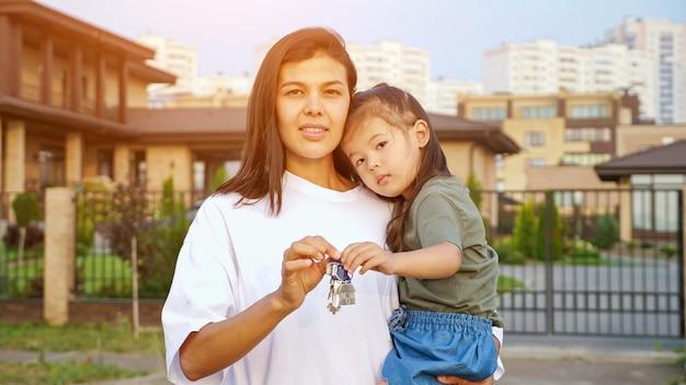 Wesoła kobieta pokazuje klucze do nowego mieszkania trzymając w ramionach małą koreańską córkę przed domem jednorodzinnym w dzielnicy mieszkalnej miasta zbliżenie, światło słoneczne