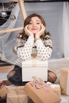 Wesoła kobieta pozuje z prezentami świątecznymi w salonie.