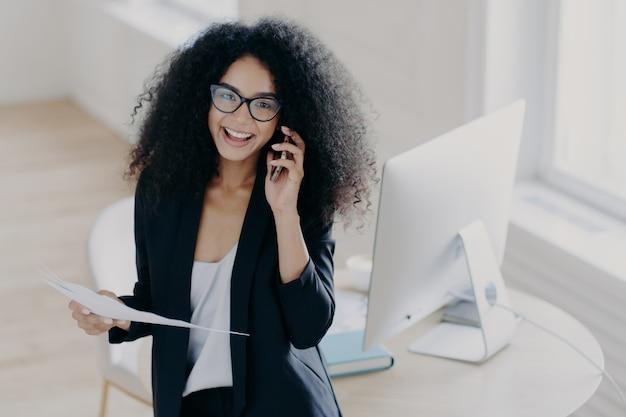 Wesoła kobieta pracownik firmy dzwoni do partnera, trzyma dokumenty papierowe, nosi okulary optyczne i elegancki garnitur