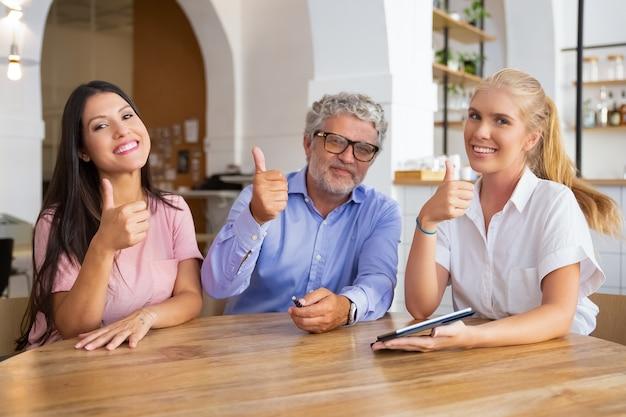 Wesoła kobieta profesjonalistka z tabletem spotkanie przy stole z zadowolonymi klientami
