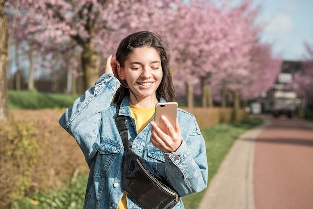 Wesoła kobieta rasy mieszanej korzystająca z telefonu na ulicy w celu wykonania połączenia wideo lub zamówienia online.