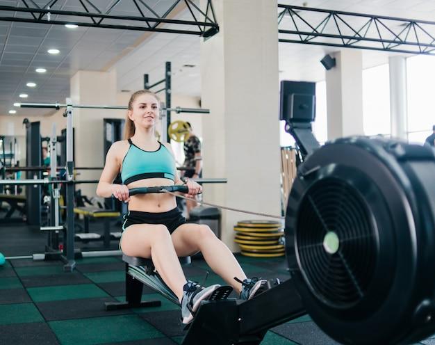 Wesoła kobieta robi ćwiczenia na maszynie do symulacji wioślarstwa w siłowni w odzieży sportowej.