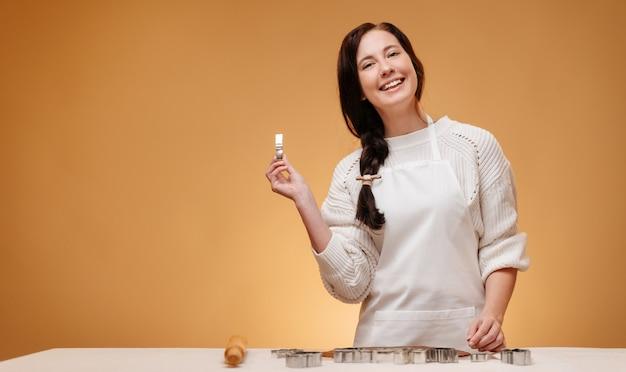 Wesoła kobieta robi świąteczne pieczenie domowych ciasteczek za pomocą metalowych foremek na żółtej formie