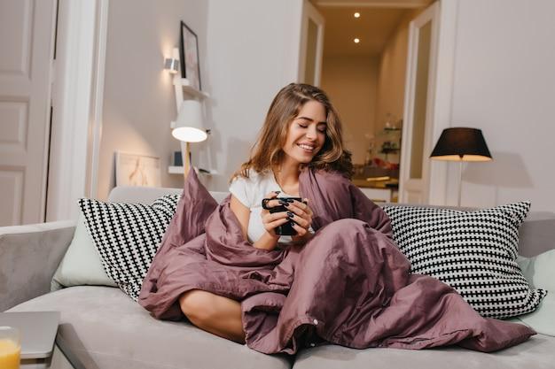 Wesoła kobieta siedzi na kanapie z kocem i poduszkami i uśmiecha się