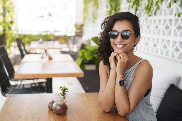 Wesoła kobieta siedzi na tarasie kawiarni w okularach przeciwsłonecznych