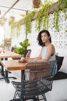 Wesoła kobieta siedzi na tarasie kawiarni