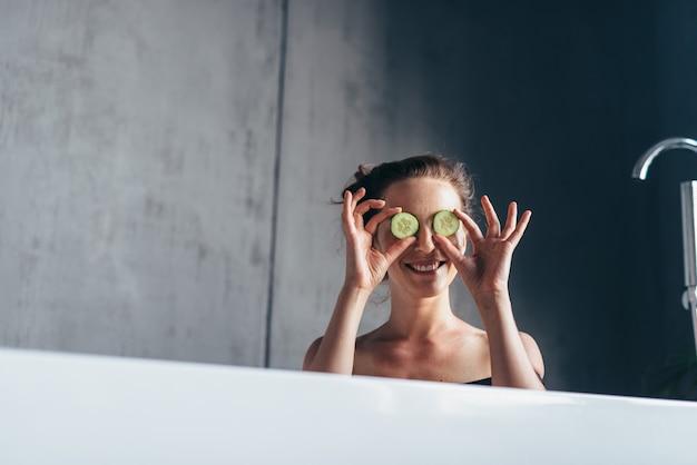 Wesoła kobieta siedzi w wannie i trzyma przed twarzą plasterki ogórka.