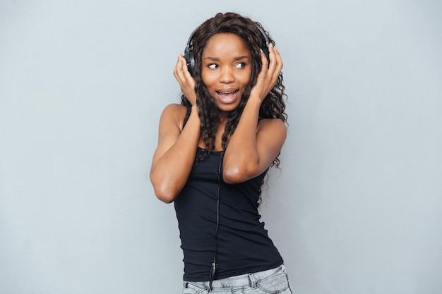 Wesoła kobieta słucha muzyki w słuchawkach i odwraca wzrok przez szarą ścianę