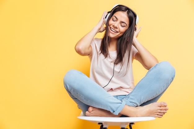 Wesoła kobieta słucha muzyki w słuchawkach nad żółtą ścianą