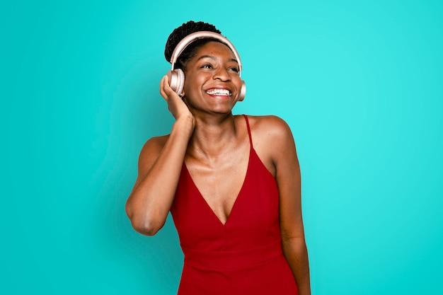 Wesoła kobieta słuchająca muzyki przez cyfrowe urządzenie słuchawkowe