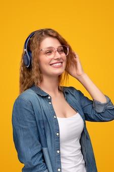 Wesoła kobieta, słuchanie muzyki w słuchawkach