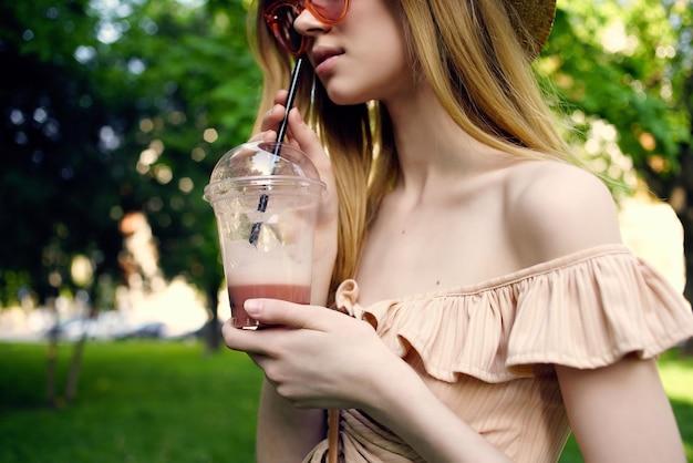 Wesoła kobieta spacery w parku na świeżym powietrzu przy drinku styl życia. zdjęcie wysokiej jakości