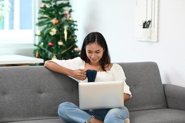 Wesoła kobieta spędzająca weekend w domu przy kawie i korzystaniu z laptopa na kanapie.