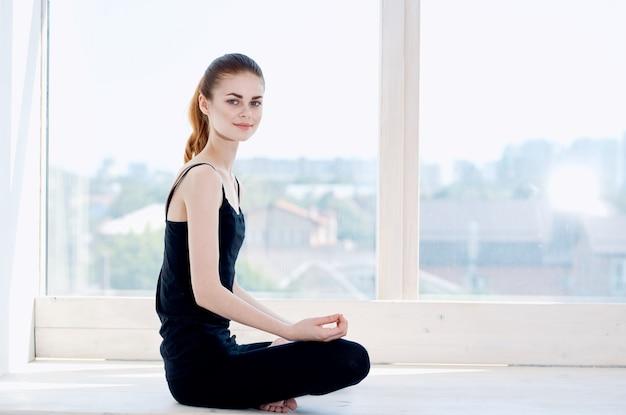 Wesoła kobieta sportive w pobliżu okna ćwiczenia relaks medytacja. zdjęcie wysokiej jakości