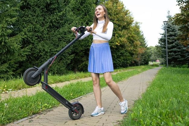Wesoła kobieta stawia swój skuter elektryczny na jednym kole