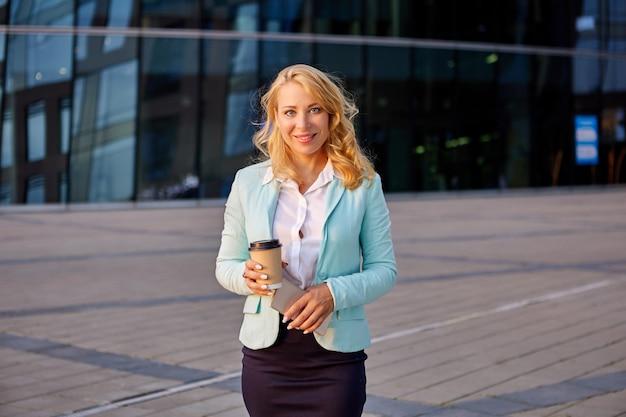 Wesoła kobieta stoi na zewnątrz w garniturze i przy filiżance kawy