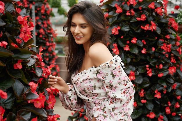 Wesoła kobieta stojąca wśród kwitnących kwiatów