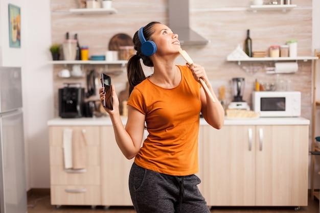 Wesoła kobieta tańczy i śpiewa rano w kuchni