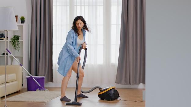 Wesoła kobieta tańczy podczas czyszczenia podłogi za pomocą odkurzacza