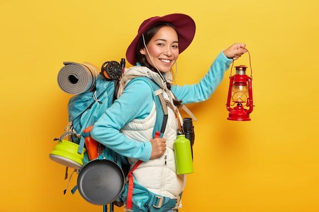 Wesoła kobieta trekker trzyma lampę naftową, nosi kapelusz i odzież codzienną, odpoczywa w lesie, nosi plecak