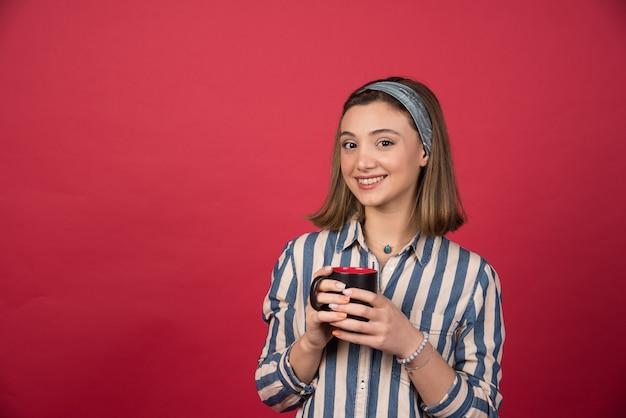 Wesoła kobieta trzyma filiżankę kawy i pozuje do przodu