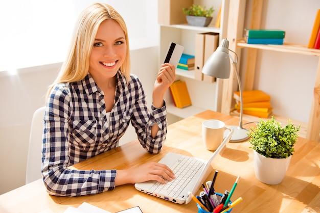 Wesoła kobieta trzyma kartę kredytową i robi bankowość