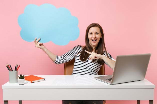 Wesoła kobieta trzyma niebieski pusty pusty say chmura dymek pracuje na białym biurku z laptopem pc na białym tle na pastelowym różowym tle. koncepcja kariery biznesowej osiągnięcia. skopiuj miejsce na reklamę.