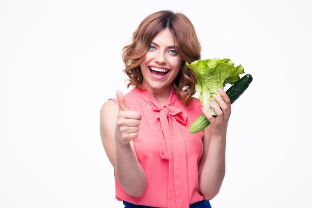 Wesoła kobieta trzyma sałatkę i ogórek