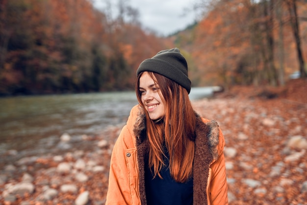 Wesoła kobieta turysta w kurtce jesień las rzeczny charakter