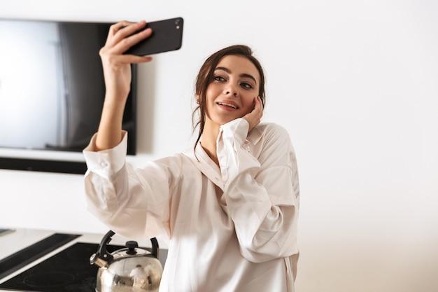 Wesoła kobieta ubrana w jedwabne ubrania, biorąc zdjęcie selfie na czarnym smartfonie, stojąc w kuchni rano