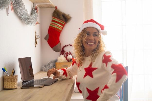 Wesoła kobieta uśmiecha się podczas świąt bożego narodzenia z laptopem