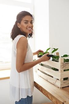 Wesoła kobieta uśmiechnięta przygotowuje się do cięcia łodyg roślin na białej ścianie i oknie